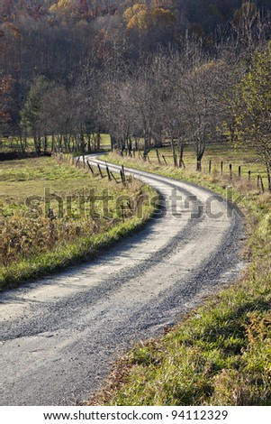 Beautiful tree lined dirt or unpaved S curve road with rustic fence - stock photo