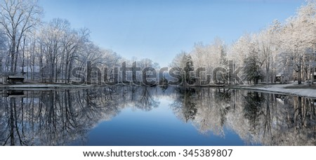 Beautiful trees with snow clinging to the branches against a bright blue sky reflecting into a calm lake.