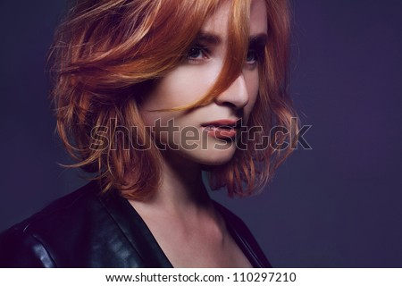 Beautiful trendy girl in fashionable outfit in a studio posing