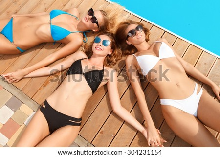 Beautiful trio. Three sexy young girlfriends lying head to another at poolside during summer vacation. - stock photo