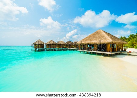 Beautiful tropical beach and sea with coconut palm tree on blue sky in Maldives island - Boost up color Processing - stock photo