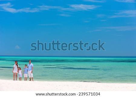 Beautiful tropical beach landscape with a family of four enjoying summer vacation - stock photo
