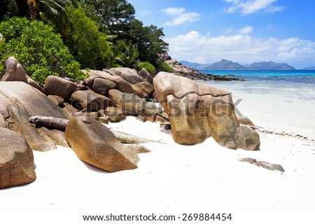 Beautiful tropical beach on La Digue, Seychelles islands. Sunny day, blue sky, turquoise ocean and amazing rocks. - stock photo
