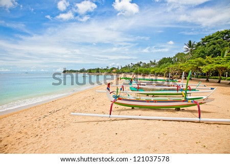 Beautiful tropical beach with fisherman's boats in Nusa Dua on Bali, Indonesia. - stock photo