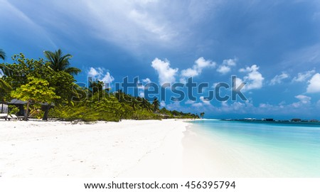 Beautiful tropical beach with palm trees, white sand, turquoise ocean water and blue sky at Kuredu, Maldives - stock photo
