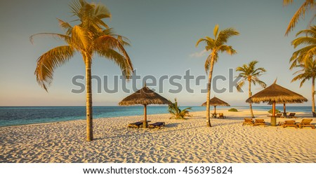 Beautiful tropical beach with palm trees, white sand, turquoise ocean water and blue sky at Kuredu, Maldives