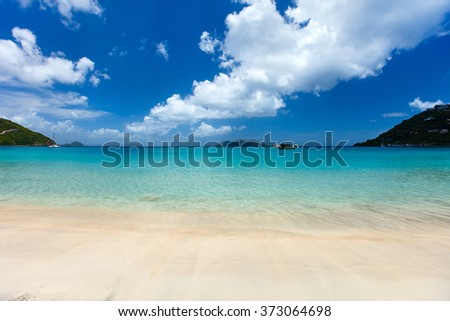 Beautiful tropical beach with palm trees, white sand, turquoise ocean water and blue sky at Tortola, British Virgin Islands in Caribbean - stock photo