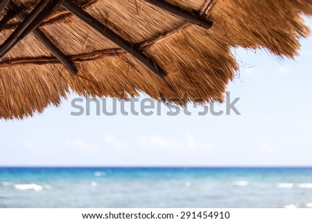 Beautiful tropical beach with white sand and palapa (thatched roof) in the Caribbean, Mexico. Summer beach background. - stock photo