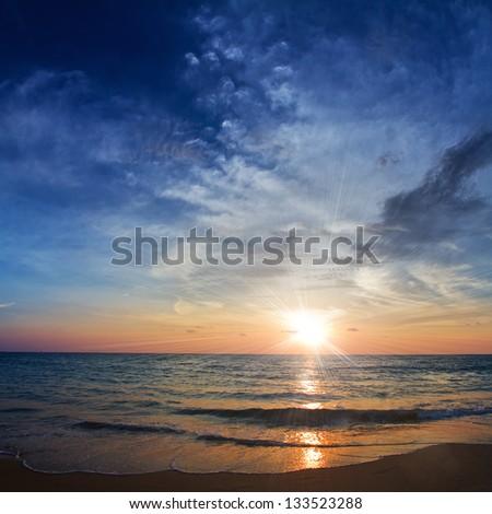 beautiful tropical beach with yellow sand breaking splashing shorebreak under sunset - stock photo