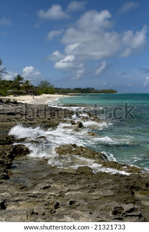 Beautiful tropical shoreline with clear green water crashing into volcanic rock. - stock photo
