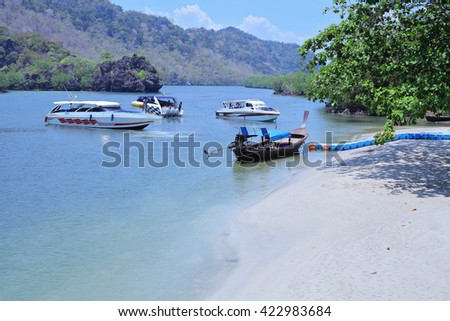 Beautiful tropical white sand beach, longtail boats near Tarutao national marine  park and Koh Lipe in Satun, Thailand.  - stock photo