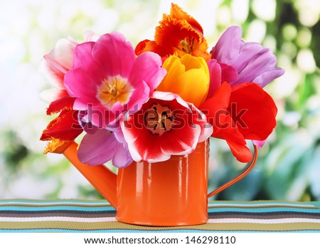 Beautiful tulips in bouquet on table on bright background - stock photo