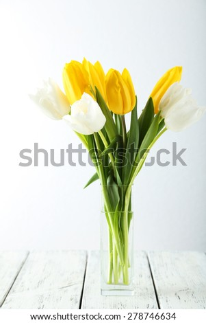 Beautiful tulips in vase on white wooden background - stock photo