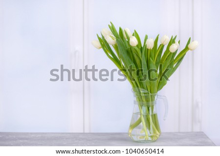 Beautiful tulips on table in the room with copy space