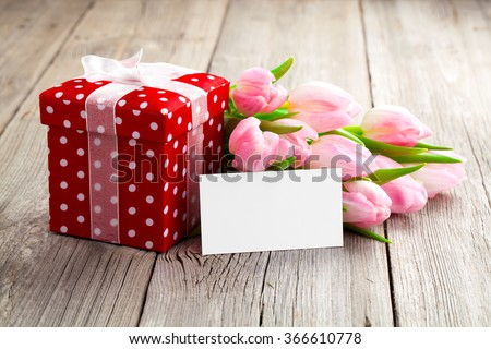 beautiful tulips with red polka-dot gift box. happy mothers day, romantic still life, fresh flowers. on wooden background - stock photo