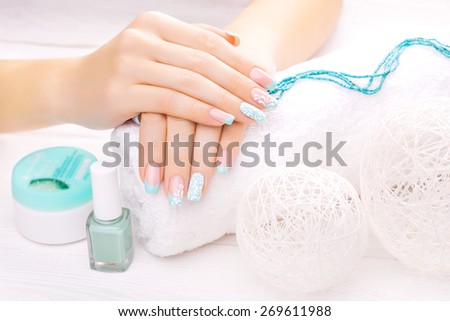 beautiful turquoise french manicure with light towel - stock photo