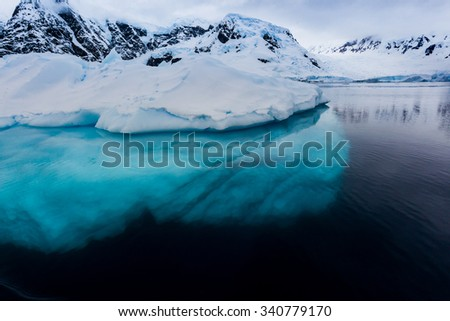 Beautiful turquoise ice below surface glacier in Antarctica - stock photo