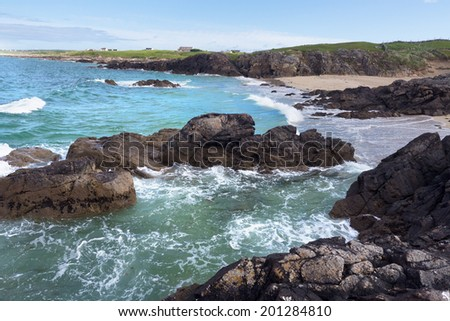 Beautiful turquoise water splashes onto jagged rocks on the shore at Clifden Bay, Connemara, Ireland. - stock photo