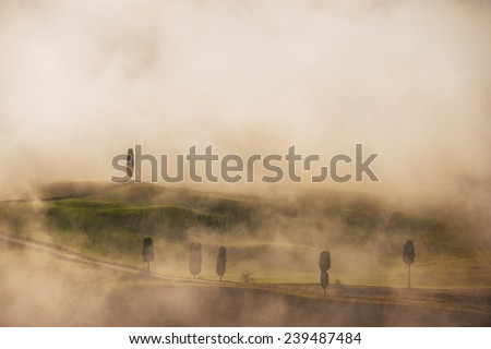 Beautiful Tuscan landscape surrounded by fog in December atmosphere - stock photo