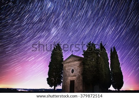 Beautiful Tuscany night landscape with star trails on the sky, cypresses and a chapel. Natural outdoor amazing fantasy background. - stock photo