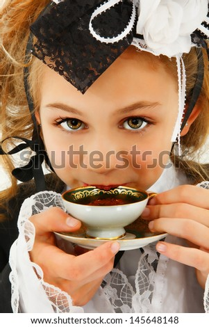 Beautiful tween girl in fantasy cosplay fashion sipping tea. - stock photo