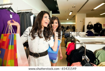Beautiful twin sisters holding colourful gift bags shopping in a clothes store - stock photo