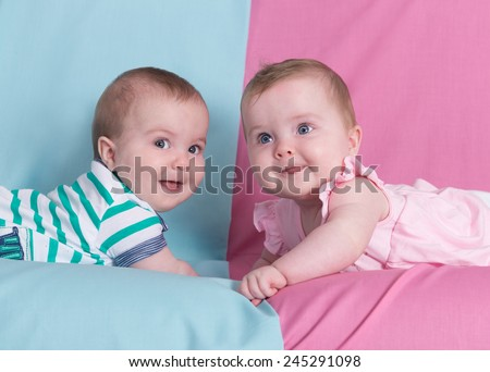 Beautiful twins on pink and blue.Brother and sister - stock photo