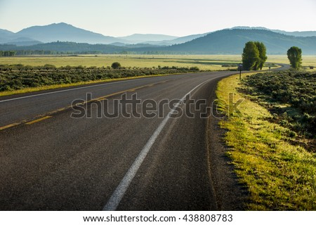 Beautiful twisting curving highway road drive in Tetons National Park with mountains and green scenery landscape