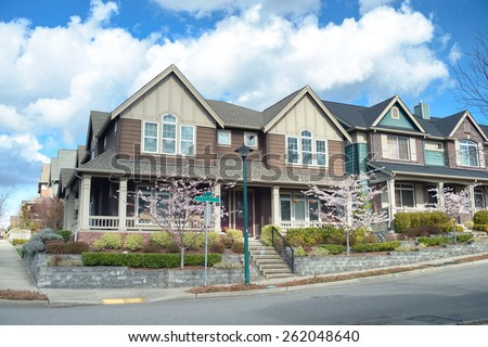 Beautiful two story american houses on the corner of the street. There is porch visible, nice landscaping, sidewalk and spring trees. - stock photo