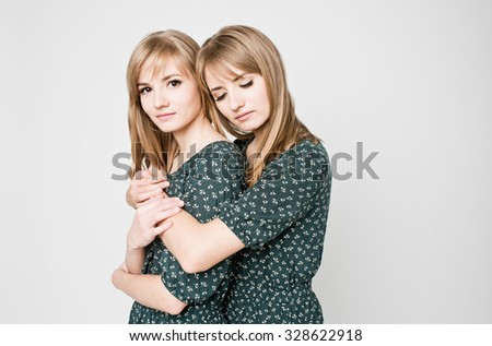 Beautiful two twins sisters together - stock photo