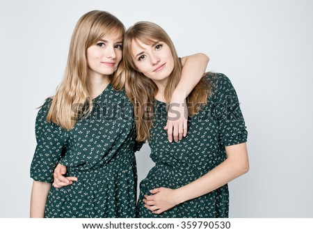 Beautiful two twins sisters together holding each other in hugs - stock photo