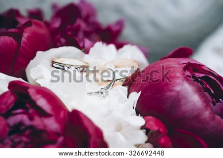 Beautiful two wedding rings and one engagement on a tender pink and white peony flowers - stock photo