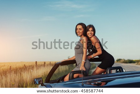 Beautiful two women sitting in a convertible, enjoying a trip on a luxury modern car with an open roof.
