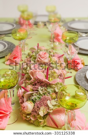 Beautiful twotone flower arrangement in soft pink and green on a christmas dinner table - stock photo