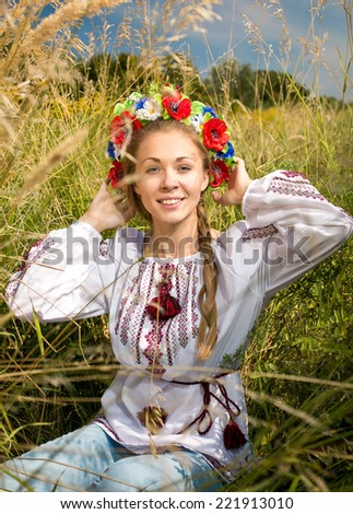 Beautiful ukrainian girl in national clothes sitting on meadow - stock photo