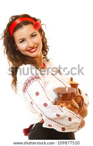 Beautiful ukrainian young woman in native costume holding earthenware pots over white background - stock photo