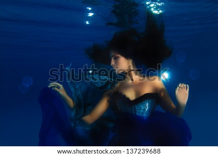 Beautiful underwater fashion model with dark long hair playing with blue fabric - stock photo