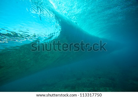 Beautiful underwater view of clear blue wave - stock photo