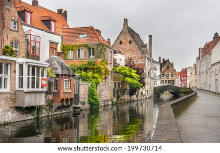Beautiful unique buildings alongside a canal in Bruges, Belgium  - stock photo