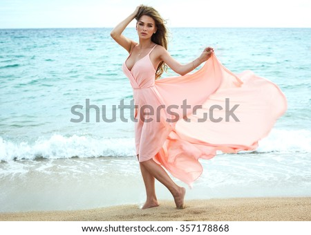 Beautiful unusual woman walking on the beach and posing in red dress  - stock photo