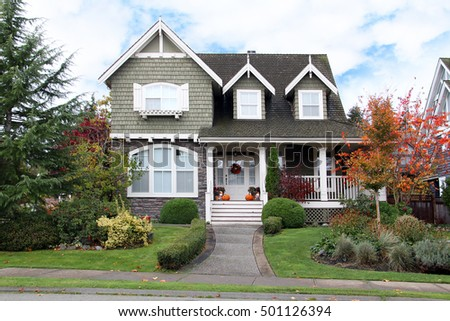 Beautiful upscale house in Canada. Autumn scene, Halloween pumpkins on the porch.