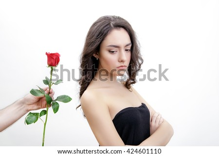 Beautiful upset girl receives one red rose. She looks at the flowers. She is looking over her shoulder. Men's hand holding one rose. Girl is white with bushy brown hair. Isolated on white background. - stock photo