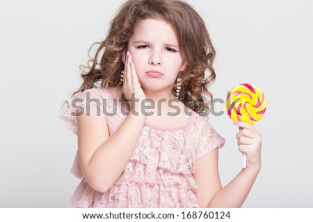 Beautiful upset little girl with big candy lollipop isolated. Cute little girl with tooth ache. Sad child with sugar candy in studio.  - stock photo