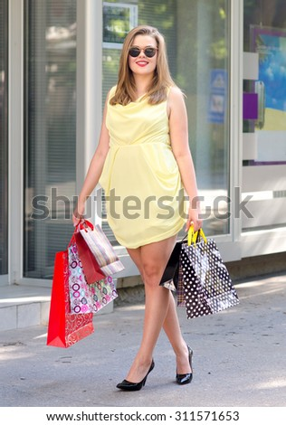 Beautiful urban girl walking down the street after shopping on sunny summer day.