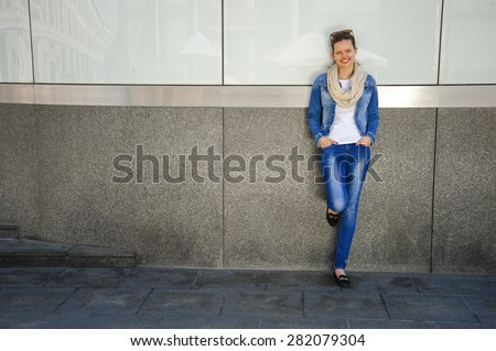 Beautiful urban woman, girl standing by the wall in city with jeans jacket - stock photo