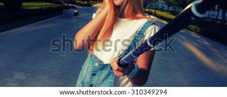Beautiful urban woman is taking selfie with selfie stick. Filtered image. Instgram color. Copyspace. - stock photo