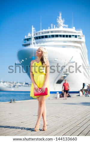 Beautiful Vacationing Woman in a dock, big cruise ship on background - stock photo