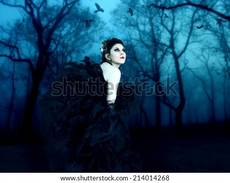 Beautiful vampire walks in the night forest. - stock photo