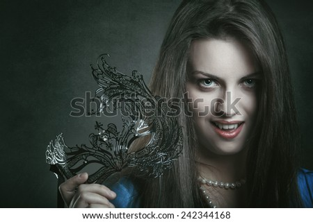 Beautiful vampire with venetian mask and evil expression  . Halloween and horror - stock photo