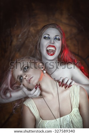 Beautiful vampire woman and her victim in the hell - stock photo